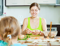 Woman with a child making fish salmon stuffing dumplings Stock Image