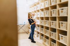 Woman with a child near the shelf with baskets stock photos