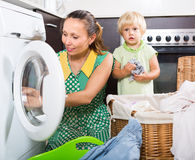 Woman with child near washing machine Royalty Free Stock Photo