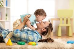 Woman with baby playing together on cozy carpet at home. Woman with child one year old playing on cozy carpet in living room Stock Photo