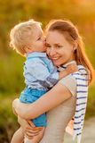 Woman and child outdoors at sunset. Boy kissing his mom. Happy women and child having fun outdoors.  Family lifestyle rural scene of mother and son in sunset Stock Photography