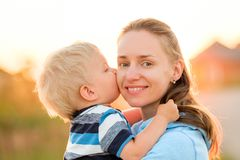 Woman and child outdoors at sunset. Boy kissing his mom. Royalty Free Stock Photography
