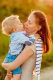 Woman and child outdoors at sunset. Boy kissing his mom. Happy women and child having fun outdoors.  Family lifestyle rural scene of mother and son in sunset Royalty Free Stock Photo