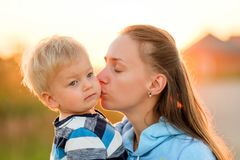 Woman and child outdoors at sunset. Mother kissing her son. Happy women and child having fun outdoors.  Family lifestyle rural scene of mother and son in sunset Royalty Free Stock Photography