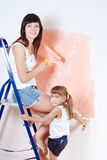 The woman and the child paint the wall Royalty Free Stock Photography