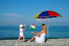 Woman and child play a ball at coast. The woman and the child sit under an umbrella and play a ball at coast Royalty Free Stock Image