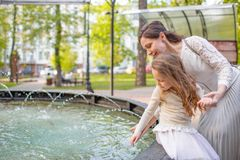 Woman with child playing against splashes of water in the summer. Mother and daughter at the fountain in the park Stock Image