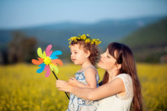 Woman and child playing. With toy wind turbine in summer field Stock Photo