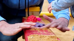 Woman and child playing with sand. In the sandbox stock video