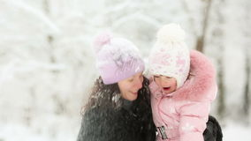 Woman and child playing with snow in winter stock footage