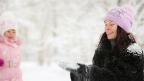 Woman and child playing with snow in winter stock video footage