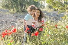 A woman and a child playing with some poppies. A women an a child playing with some poppies at sunset Royalty Free Stock Image