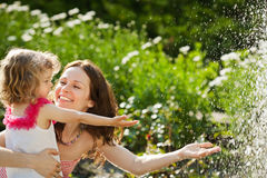 Woman with child playing in spring park. Woman with child playing against splashes of water in the summer Royalty Free Stock Image
