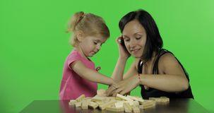 Mother and daughter plays the jenga. Child making a tower from wooden blocks stock footage