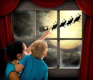 Woman with child pointing at Santa Claus. On sky Stock Photo