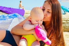 Mother kissing baby in swimsuit on beach Royalty Free Stock Photos