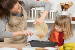 Woman and child pouring cream into baking loaf Royalty Free Stock Photo