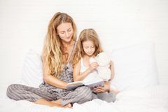 Woman with child reading book Stock Photos