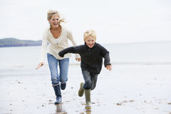 Woman and child running on beach