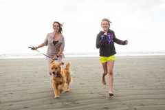 Woman and child running with a dog Royalty Free Stock Photos