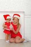 Woman with a child in Santa costumes look gift Stock Image