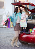 A woman with a child after shopping load the car Stock Images