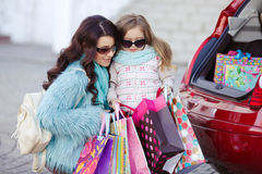 A woman with a child after shopping load the car Royalty Free Stock Photos