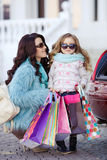 A woman with a child after shopping load the car Stock Photos