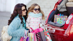 A woman with a child after shopping load the car. Beautiful young women with long curly hair,in a fur jacket blue,in dark glasses,with his little daughter,curly Stock Photography