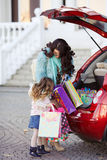 A woman with a child after shopping load the car. Beautiful young women with long curly hair,in a fur jacket blue,in dark glasses,with his little daughter,curly Royalty Free Stock Image