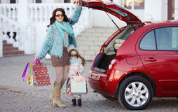 A woman with a child after shopping load the car. Beautiful young women with long curly hair,in a fur jacket blue,in dark glasses,with his little daughter,curly Stock Images