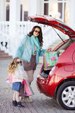 A woman with a child after shopping load the car. Beautiful young women with long curly hair,in a fur jacket blue,in dark glasses,with his little daughter,curly Royalty Free Stock Photo