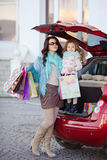 A woman with a child after shopping load the car. Beautiful young women with long curly hair,in a fur jacket blue,in dark glasses,with his little daughter,curly Royalty Free Stock Photos