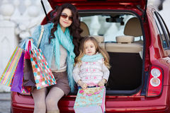 A woman with a child after shopping load the car. Beautiful young women with long curly hair,in a fur jacket blue,in dark glasses,with his little daughter,curly Royalty Free Stock Photography