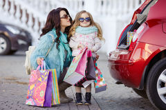 A woman with a child after shopping load the car. Beautiful young women with long curly hair,in a fur jacket blue,in dark glasses,with his little daughter,curly Stock Photo