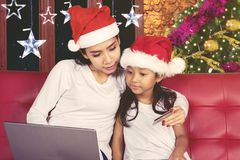 Woman and child shopping online at Christmas time. Beautiful women shopping online with her daughter while sitting on the couch. Shot at Christmas time Stock Photos