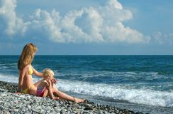 Woman and child sit on the beach Royalty Free Stock Image