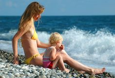 Woman and child sit on seaside Stock Photography