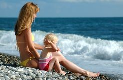 Woman and child sit on seaside Stock Images