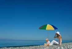 Woman and child sit under an umbrella Stock Photos