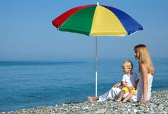 Woman and child sits under an umbrella Royalty Free Stock Photos