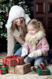 Woman and child sitting near Christmas tree. Daughter sitting on mother's lap Stock Images
