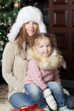 Woman and child sitting near Christmas tree. Daughter sitting on mother's lap Stock Photo