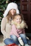 Woman and child sitting near Christmas tree. Stock Photo