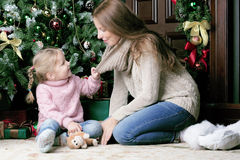 Woman and child sitting near Christmas tree. Daughter pulls the collar of his mother Stock Images