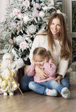 Woman and child sitting near Christmas tree. Mother and daughter happy Christmas Royalty Free Stock Photos