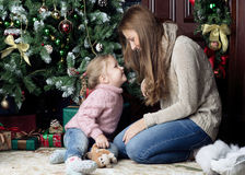 Woman and child sitting near Christmas tree. Mother and daughter looking at each other Stock Image