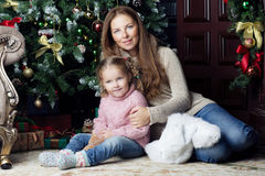 Woman and child sitting near Christmas tree. Mother and daughter sitting near the Christmas tree and smile Stock Photography