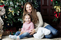 Woman and child sitting near Christmas tree. Mother and daughter sitting near the Christmas tree and smile Royalty Free Stock Photo