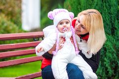 Woman with a child sitting on a park bench. Stock Photo